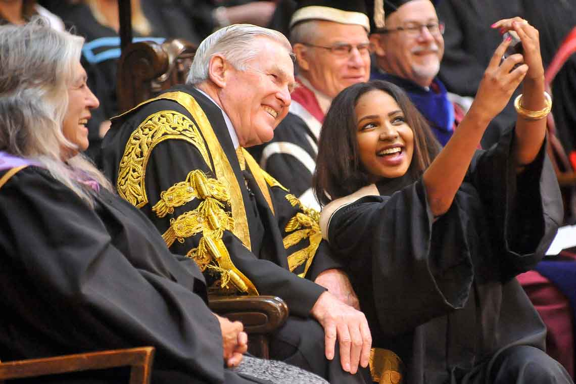 A graduating student from the Class of 2015 takes a selfie with Chancellor Michael Wilson. Photo by Ken Jones.