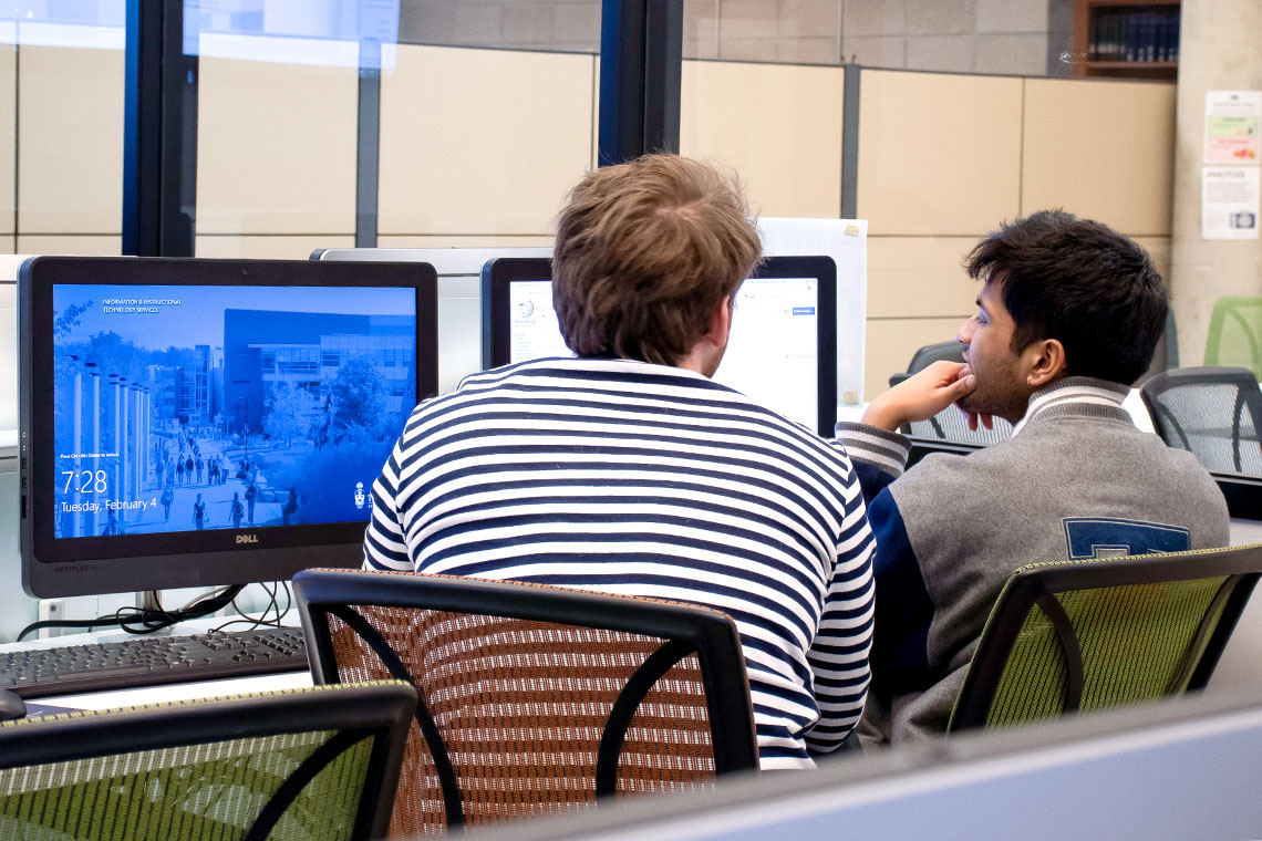 Two young men gaze thoughtfully at a computer screen in a study room full of tables and chairs