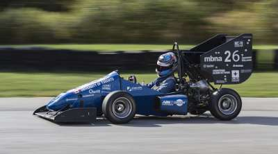 The half-sized U of T Formula SAE racing car speeds down a track. It features an open cockpit, rollbar, and huge rear wing.