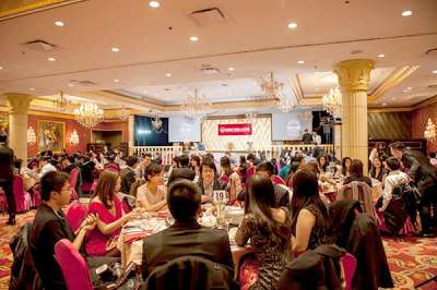 Group of Chinese alumni sit at a banquet table at an elegant dinner event.