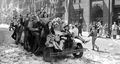 Black and white photo of a group of Canadians riding a car together at the time of the second world war