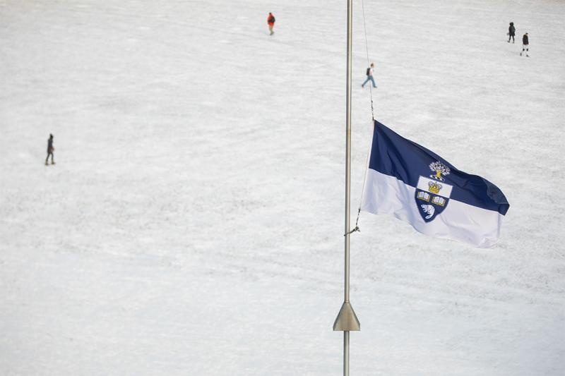 The U of T flag flies at half mast against the background of a snowy campus.