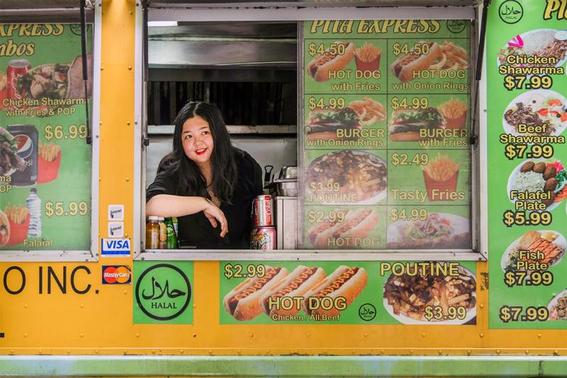 Joanna Luo smiles as she looks out the window of a food truck plastered with prices and images of burgers and fries.