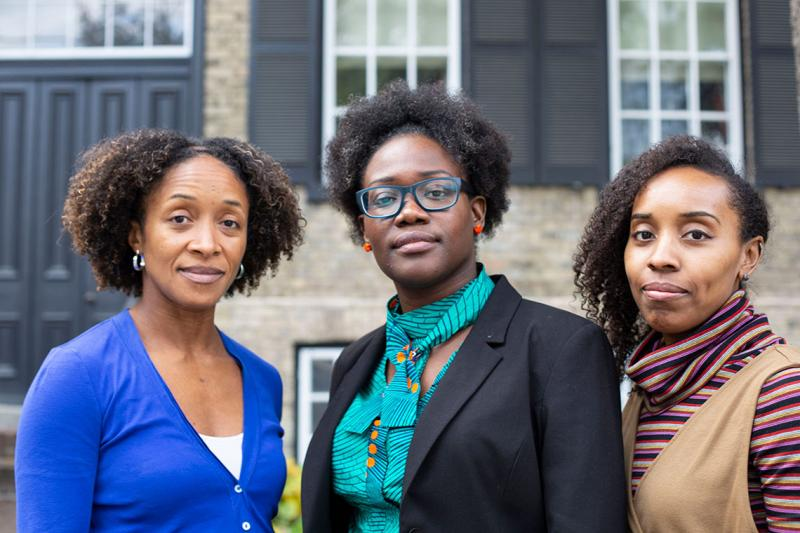 Aisha Lofters, Onye Nnorom and Nakia Lee-Foon stand outside a building, looking thoughtful.