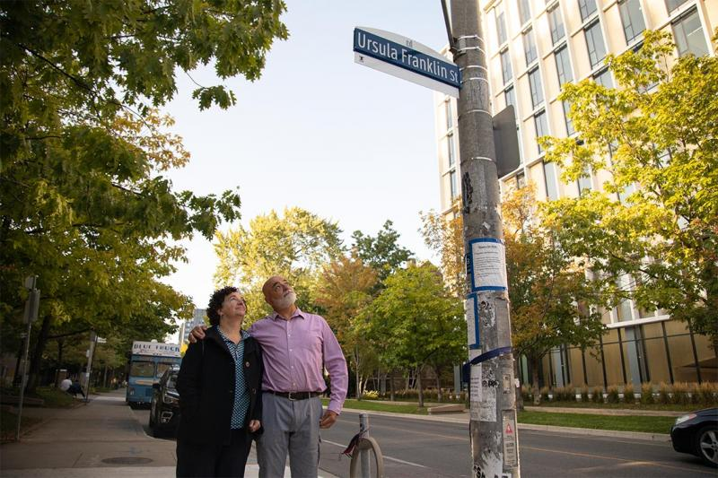 Siblings Monica and Martin Franklin look up at a sign on a light pole that reads: Ursula Franklin St.