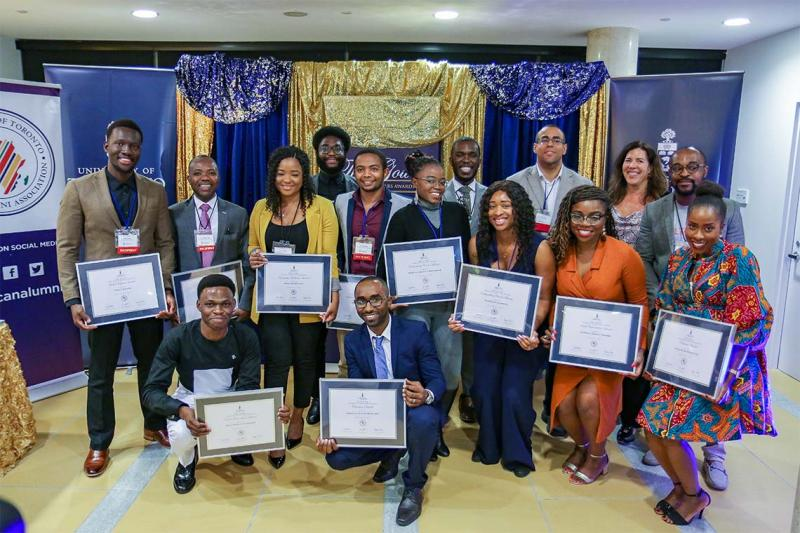 A group of 15 people pose holding framed African Scholars Awards certificates.
