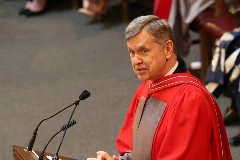 Alfred Aho talks while wearing academic robes and standing at a podium.