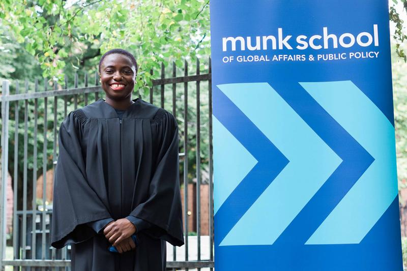 Anowa Quarcoo smiles happily. She is wearing academic robes and standing next to a sign for the Munk School.