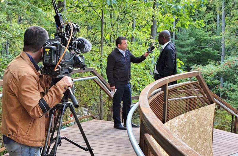 Wisdom Tettey chats with a CTV reporter on a curved wooden bridge, while a man points a large TV video camera at them.