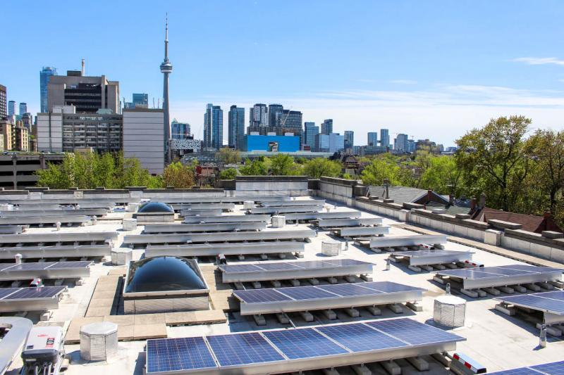 A rooftop at U of T is dotted with solar panel installations, angled to face south.
