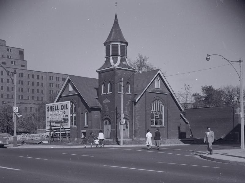 Archival photograph of First Baptist Church in the 1950s, squeezed next to a construction site and a billboard for Shell Oil.