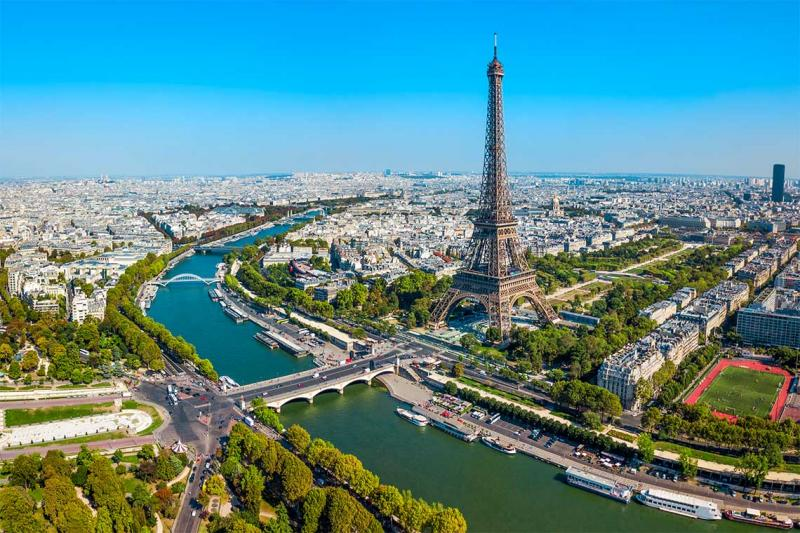 An aerial view of the Eiffel Tower, soaring above tree-lined Parisien streets on the banks of the Seine River.