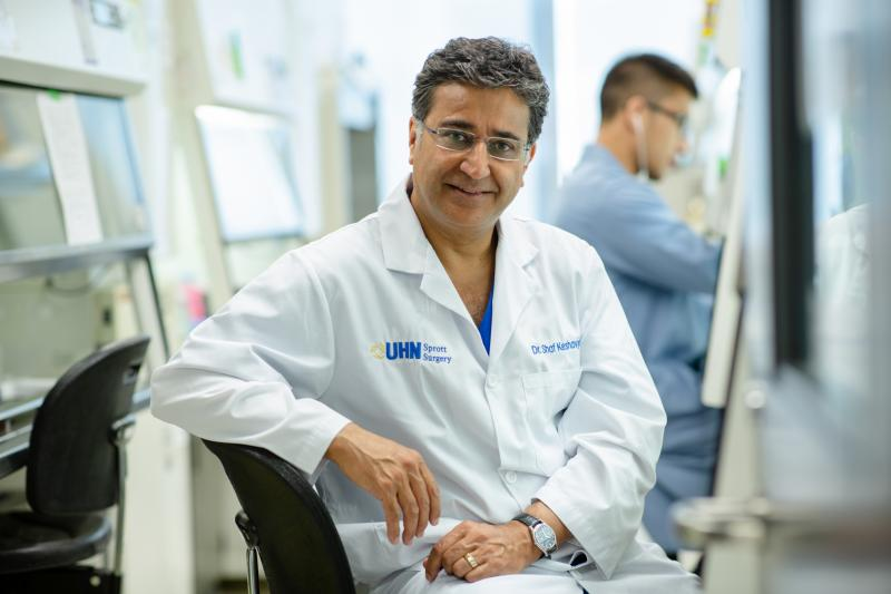 Shaf Keshavjee smiles, wearing a lab coat with the logo: UHN Sprott Surgery
