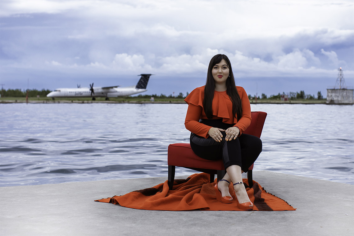 Lesley Hampton smiles as she poses in a dramatic ruffled shirt, on a dock across from a lakeside airport.