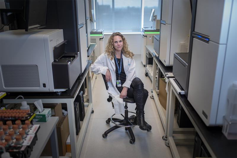 Lisa Strug sits on a chair between fridges and other lab equipment.