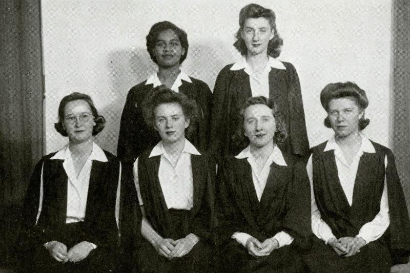 Gloria Carpenter stands in the back row of a formal photo of six women from her 1945 yearbook.