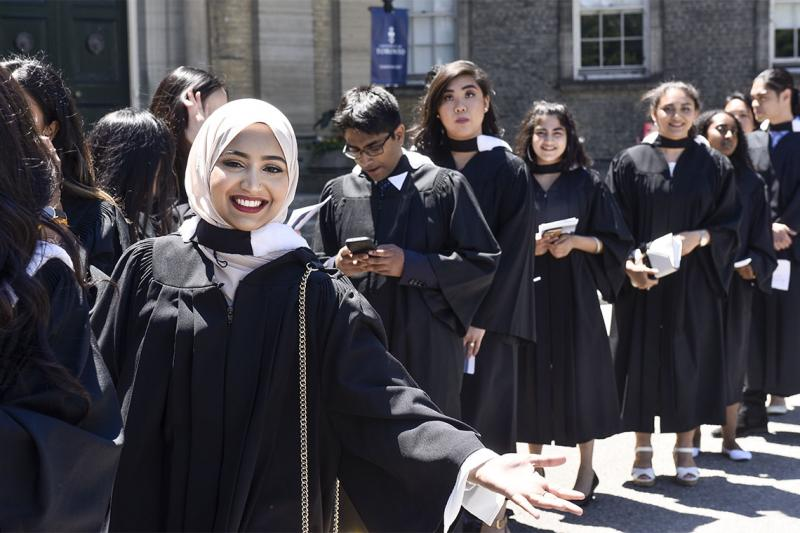 A woman smiles and gestures while standing in a line of diverse students in academic robes waiting to graduate.