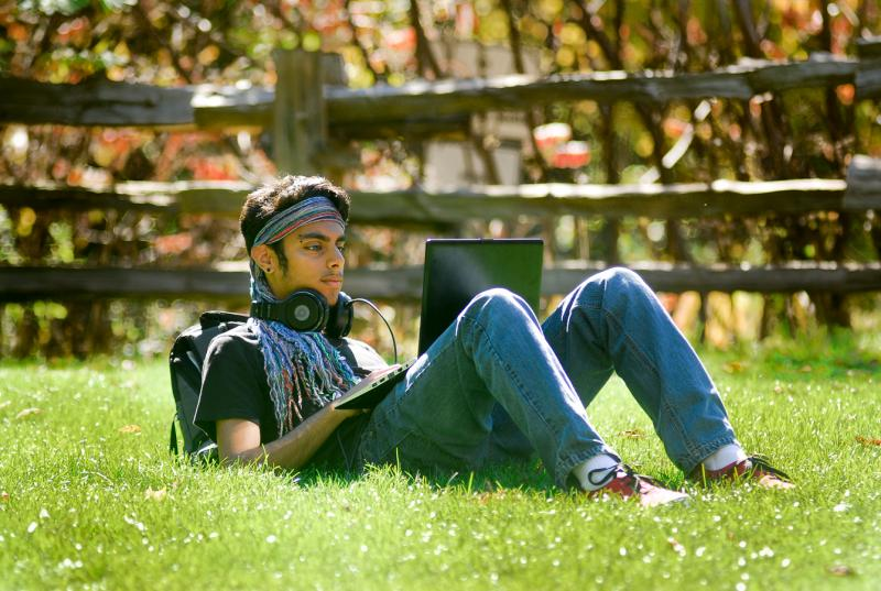 A young man sits alone outdoors on the grass, looking at his laptop screen.