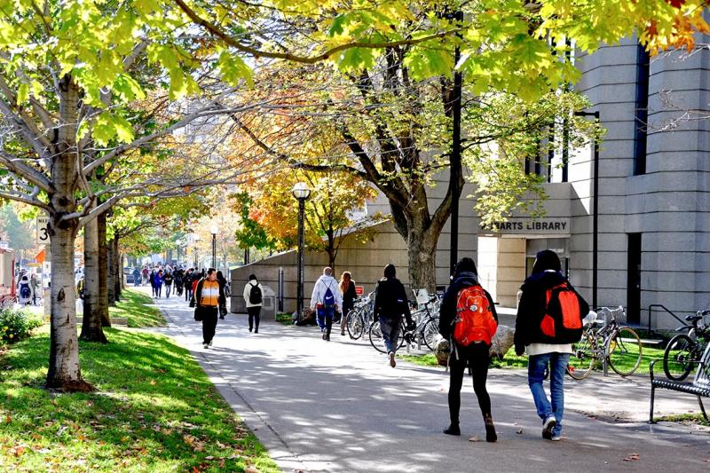 Students walk along the sidewalk outside Robarts Library under trees in spring leaf.