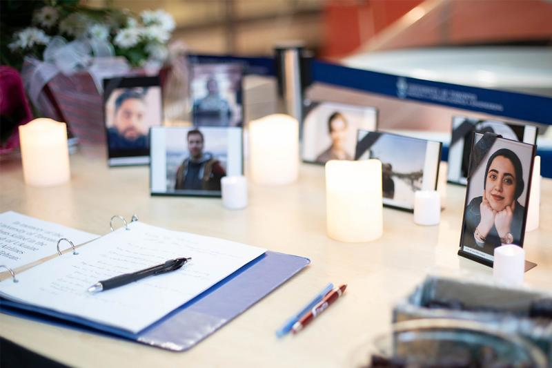 A book of condolence lies open on a table covered with candles and student photographs.