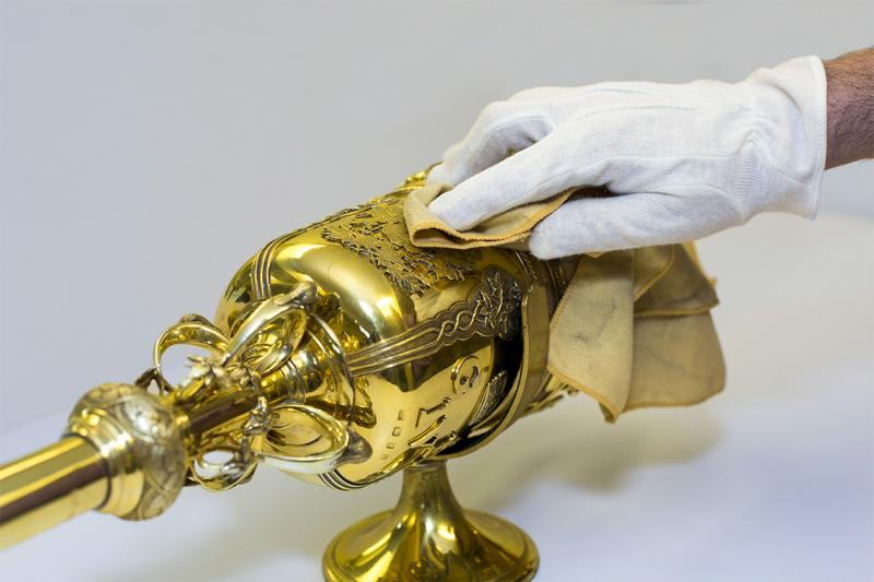 A gloved hand gently dusts the elaborate gold head of U of T's ceremonial mace.