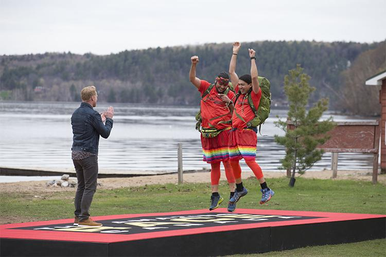 Anthony Johnson and James Makokis, wearing matching T-shirts and rainbow skirts, jump for joy on the winner's mat of Amazing Race Canada.