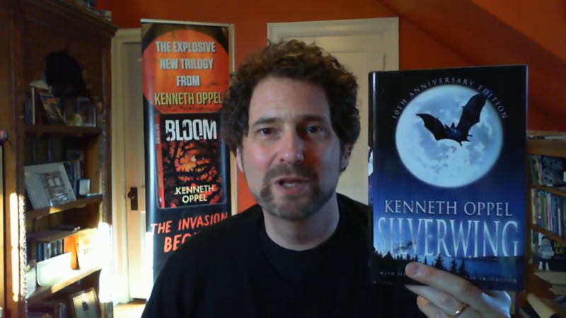 Kenneth Oppel smiles and holds up his book Silverwing in this still from a video.