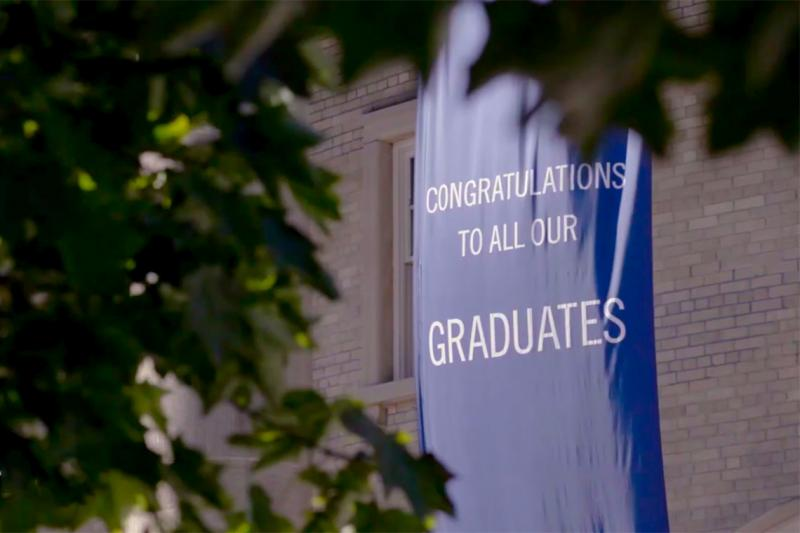A banner saying Congratulations to all our Graduates hangs outside Convocation Hall.