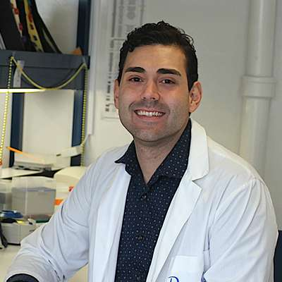Daniel Almeida smiling while sitting at his lab bench