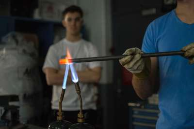 A student in safety glasses and gloves holds a steel tube in the flame of two welding torches until it glows red hot.