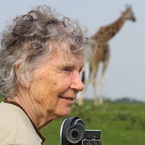 Anne Innis Dagg looks over her camera with a giraffe in the background.