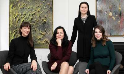 Four women smile as they sit together in a room hung with artworks.