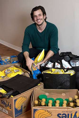 Adam Zivo smiles as he kneels in the middle of several open boxes of groceries.