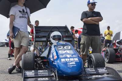 Two students stand on either side of the U of T racing car as it takes position on the start grid at the Pittsburgh International Race Complex.