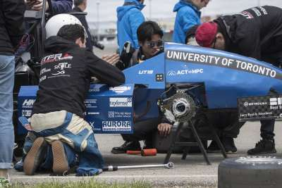The U of T Racing Team's pit crew kneel around their car, working hard on a wheel change and other fixes.