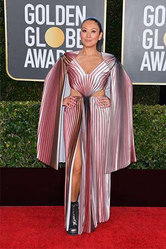 Lainey Lui smiles as she poses on the red carpet in an ombre pleated v-neck dress with caped sleeves and a high slit.
