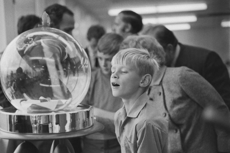 A young boy stares open-mouthed at moon rocks displayed  under a glass bubble.