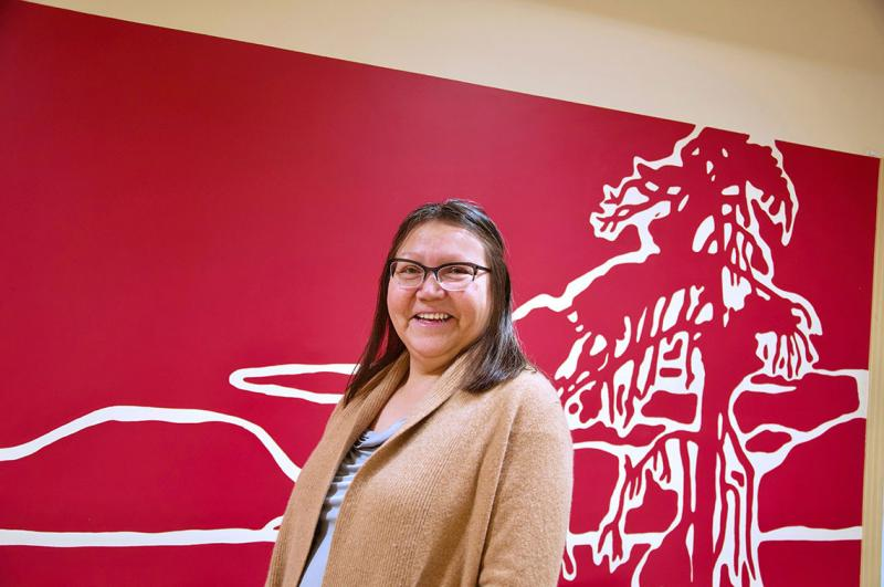Assistant Professor Brenda Wastasecoot (PhD 2017) smiling in front of artwork of a pine tree (photo by Diana Tyszko)