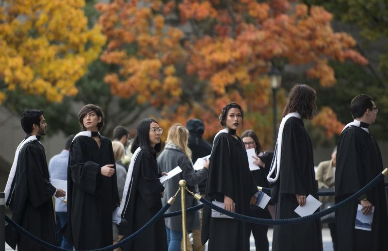Graduates line up outside Convocation Hall in front of the fall foliage (photo by Laura Pedersen)