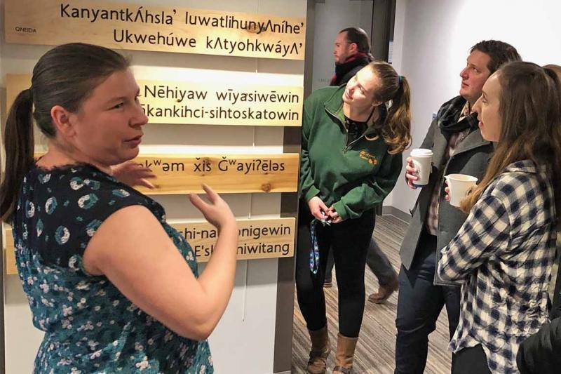 Rochelle Allan, left, acting manager of the Indigenous Initiatives Office, views the language installation -- five boards made from traditional wood and carved with Indigenous languages -- with U of T law students (photo by Lucianna Ciccocioppo)