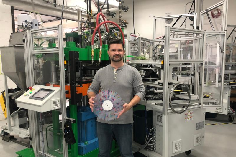 Rob Brown holds a vinyl disc with colourful markings. Behind him is a large press machine that nearly fills the room.