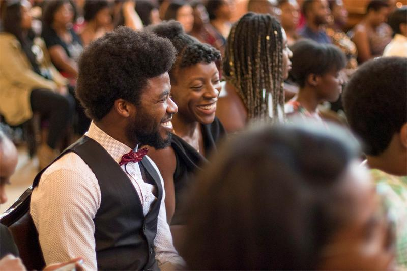 People laugh together as they sit in the audience for U of T's Black Graduation ceremony.