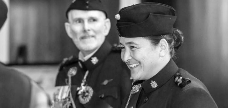 Vicky Sunohara smiles while wear a military hat and uniform with insignia on the collar.