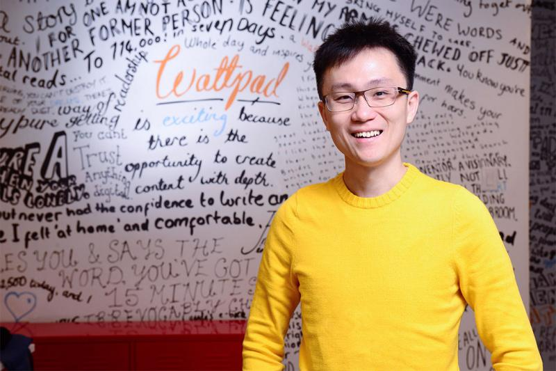 Allen Lau smiles while standing in front of a whiteboard scrawled with dozens of inspirational messages.