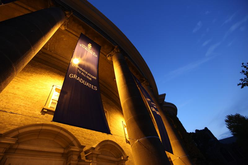 Convocation Hall glows at dusk. The banner reads: Congratulations to all our graduates.