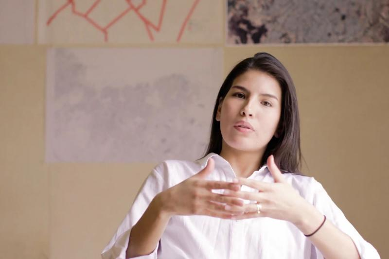 Gabriela Luna Vélez gestures while talking in front of a display of architectural drawings.