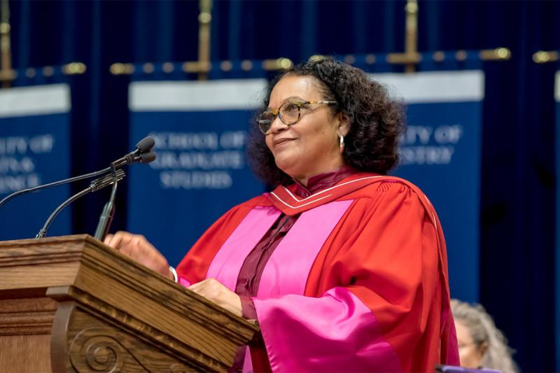 Lorna Goodison smiles while standing an a podium and wearing academic robes.