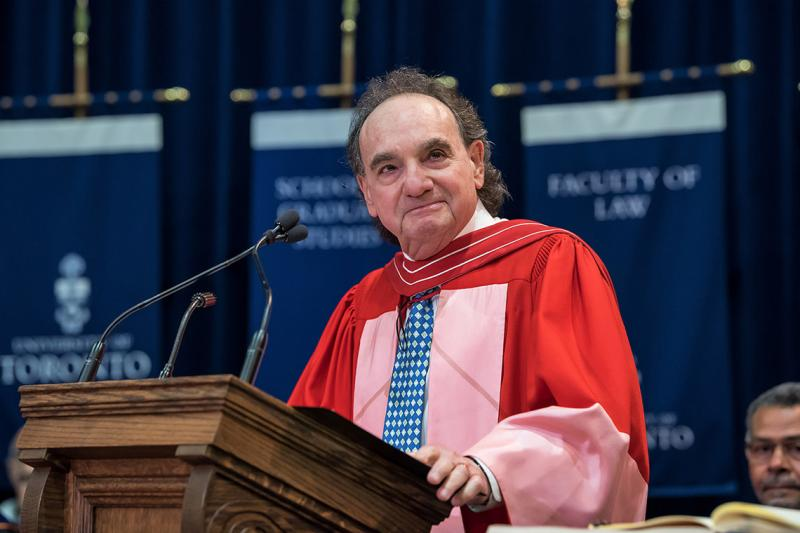 Michael Moldaver, wearing academic robes, smiles from the podium at Convocation Hall.