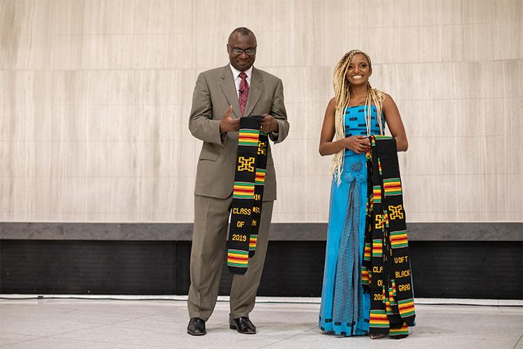 "Wisdom Tette and Kalkidan Alemayehu hold scarves in traditional African colours that read ""Class of 2019, U of T Black Grad""."