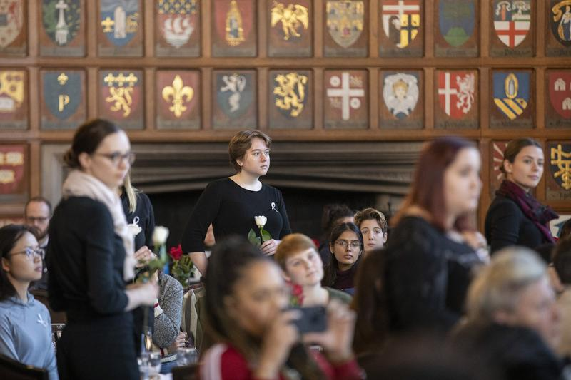 Women dressed in black and holding roses listen attentively, in a room in Hart House.